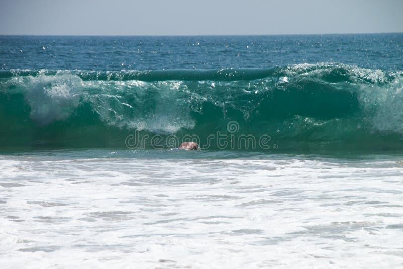 Mens die in de reusachtige grote oceaan van golfsri lanka duiken stock foto