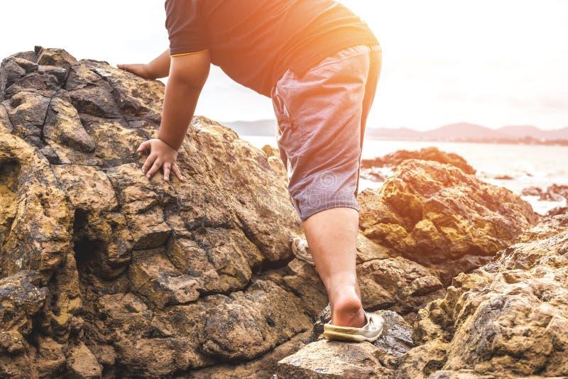 Mens die de steen op het strand beklimmen stock fotografie