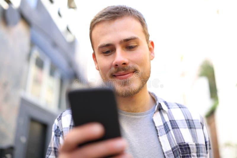 Mens die in de straat lopen die een smartphone met behulp van royalty-vrije stock foto's