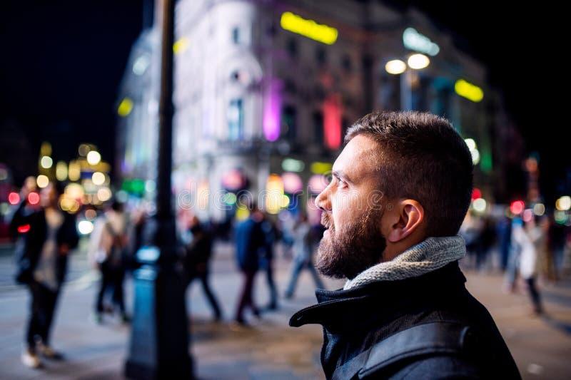 Mens die in de straten van Londen bij nacht lopen stock fotografie