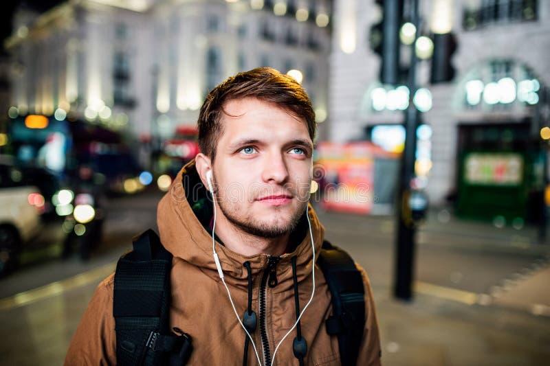 Mens die in de straten van Londen bij nacht lopen stock foto