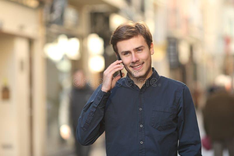 Mens die de telefoon uitnodigen die op de straat lopen stock foto's