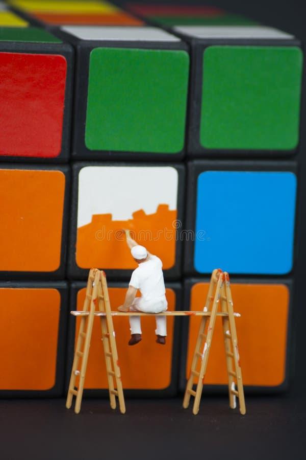 Mens die de vierkanten op een rubikskubus schilderen stock afbeelding