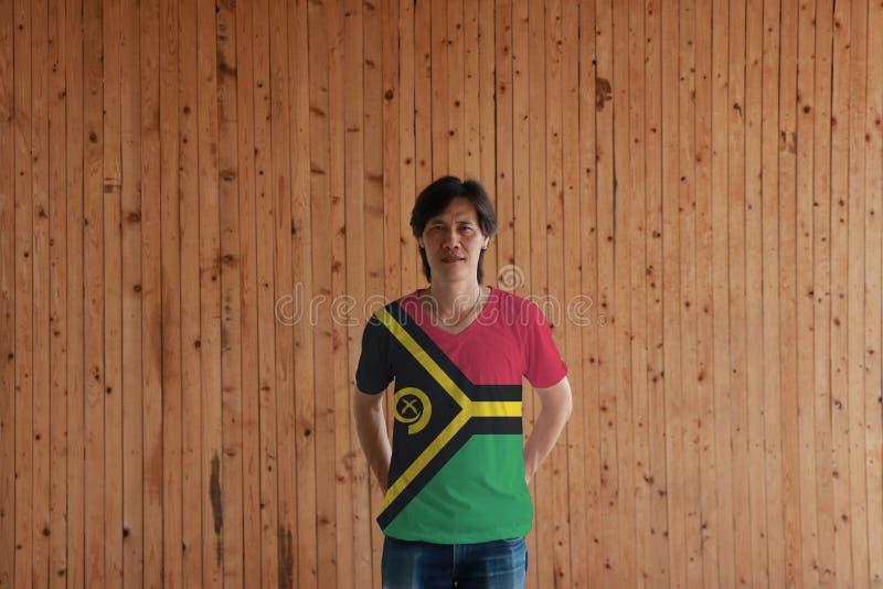 Mens die de vlagkleur van Vanuatu van overhemd dragen en zich met gekruist achter achter de bevinden overhandigt op de houten muu royalty-vrije stock afbeeldingen