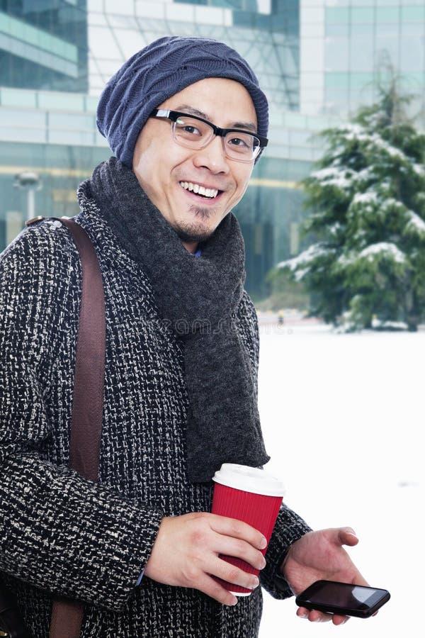 Mens die in de winterkleren koffiekop en mobiele telefoon houden stock fotografie
