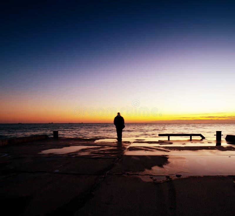 Mens die de zonsondergang kijken stock foto