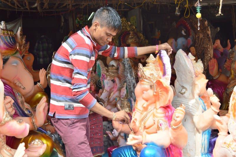 Mens die definitieve aanraking geeft aan het standbeeld van Lord Ganesha dichtbij Hollywoodbasti, Ahmedabad stock afbeelding
