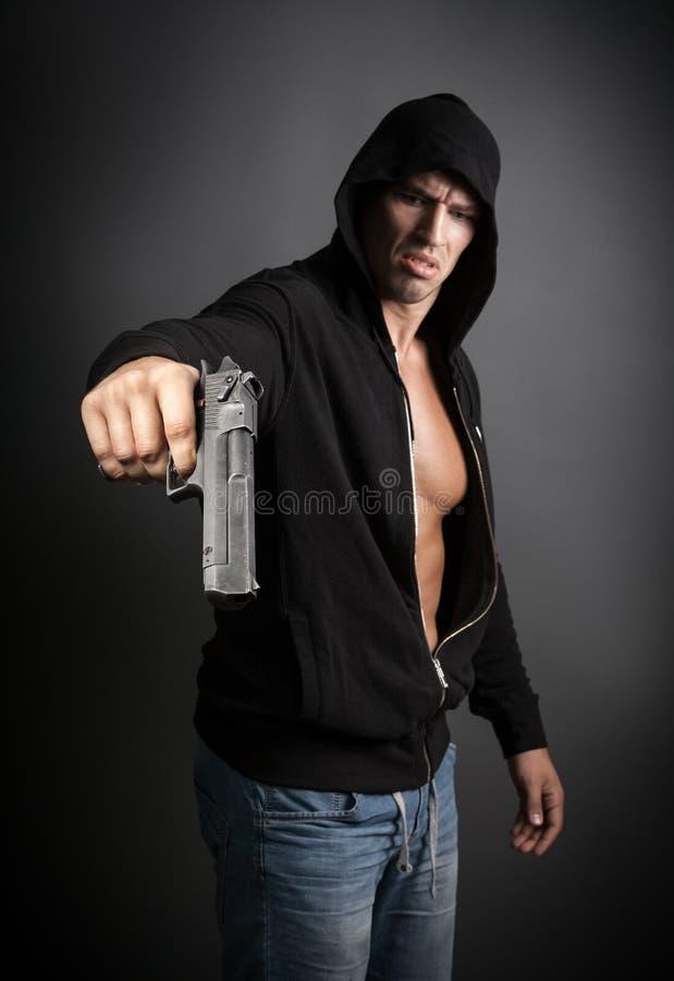 Mens die die kanon schieten op grijze achtergrond wordt geïsoleerd stock afbeelding