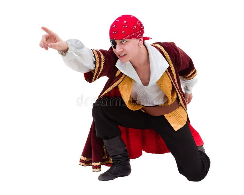 Mens die die piraatkostuum het stellen met het richten van gebaar dragen, op wit wordt geïsoleerd stock afbeelding