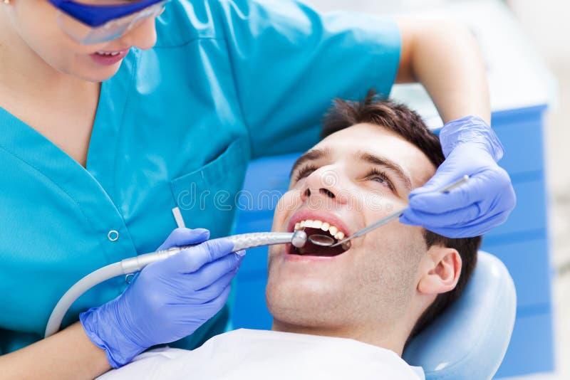 Mens die die tanden hebben bij tandartsen worden onderzocht stock foto