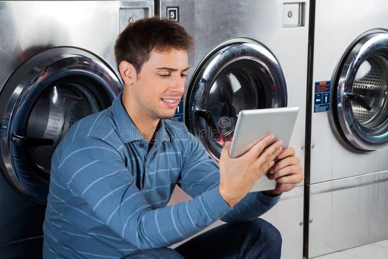 Mens die Digitale Tablet gebruiken bij Wasserij stock afbeeldingen
