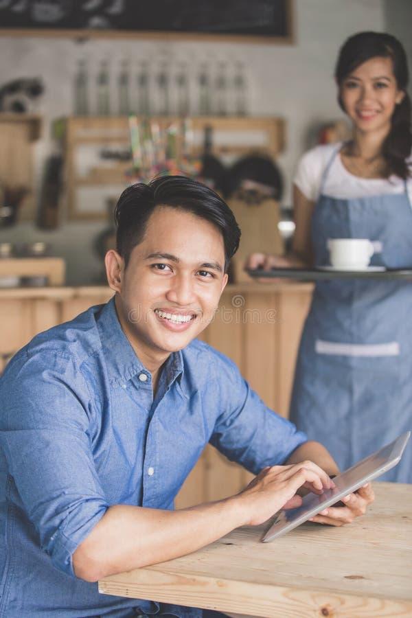 Mens die digitale tablet in koffie gebruiken royalty-vrije stock foto