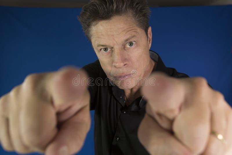 Mens die direct u met zijn te bestrijden vuisten bekijken stock fotografie