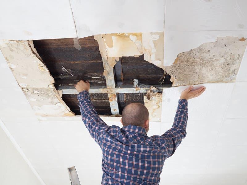 Mens die doen ineenstorten plafond herstellen royalty-vrije stock afbeeldingen