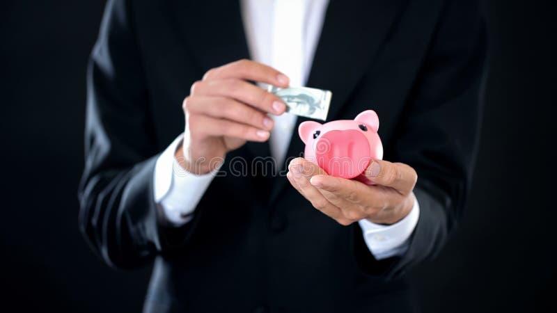 Mens die dollarbankbiljet in spaarvarken, spaarrekening, het inkomen van de bankstorting zetten stock afbeeldingen