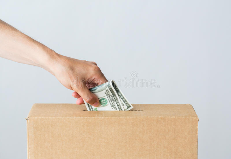 Mens die dollargeld zetten in schenkingsdoos stock afbeelding