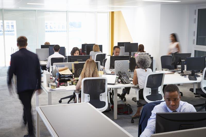 Mens die door een bezig open planbureau lopen stock afbeeldingen