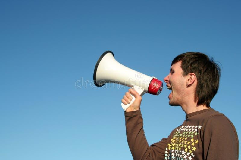 Mens die door Megafoon schreeuwt stock foto