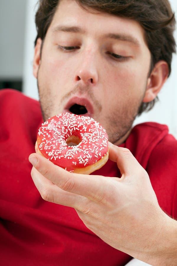 Mens die doughnut eten royalty-vrije stock foto