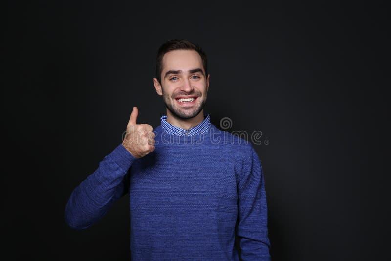 Mens die DUIM OP gebaar in gebarentaal op zwarte tonen stock fotografie