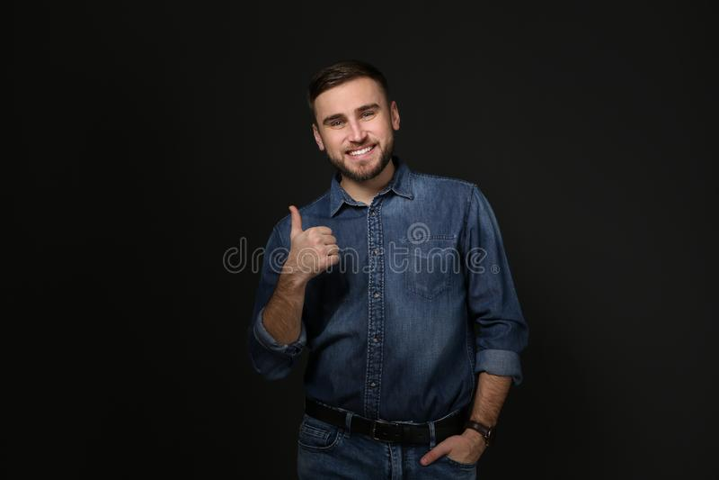 Mens die DUIM OP gebaar in gebarentaal op zwarte tonen stock foto