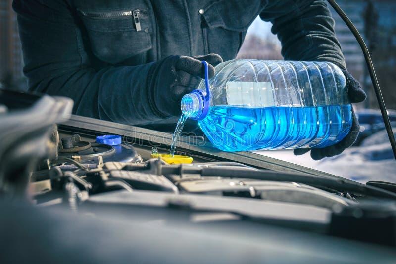 Mens die een antivriesmiddelenvloeistof in een tank van de windschermwasmachine van een auto gieten stock afbeelding