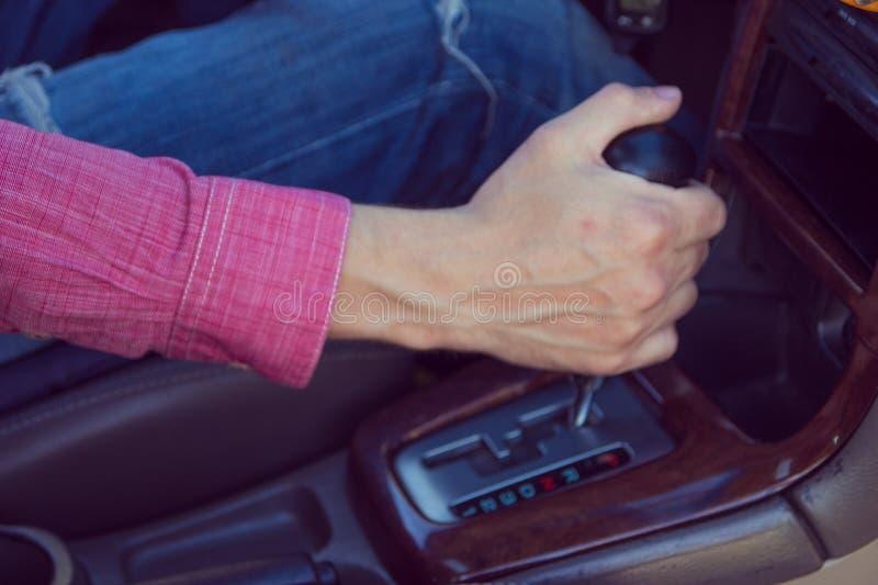 Mens die een auto drijft Handen op de transmissie stock foto's