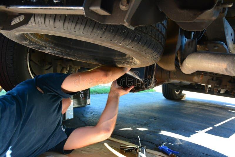 Mens die een auto of een vrachtwagen herstellen stock afbeelding