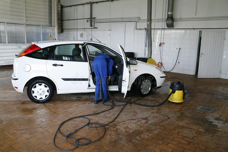 Mens die een auto schoonmaakt stock afbeelding