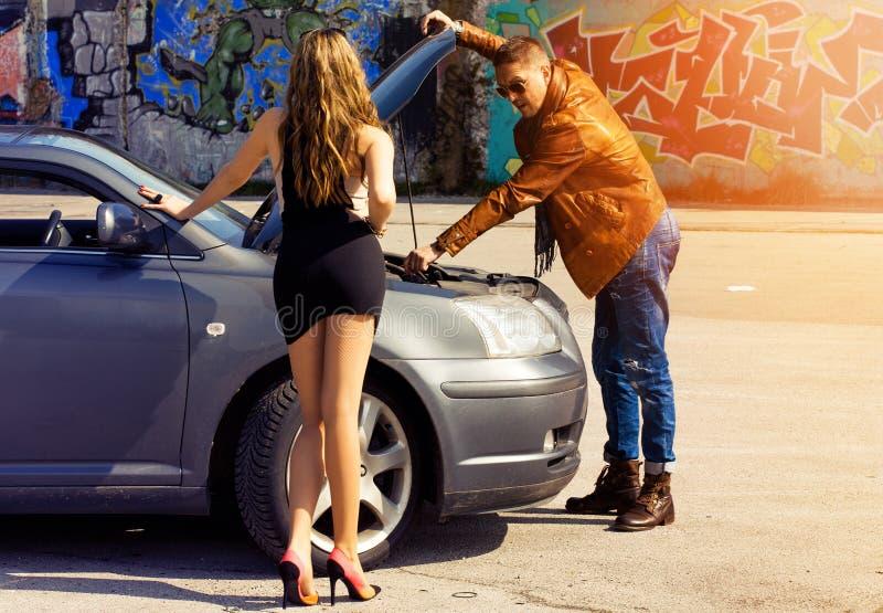 Mens die een auto voor sexy slank blondemeisje herstellen stock fotografie