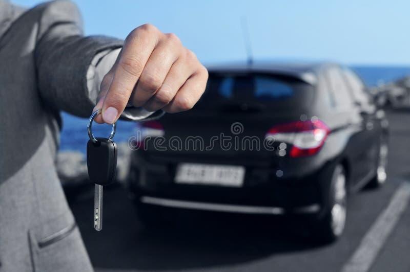 Mens die een autosleutel aanbieden aan de waarnemer royalty-vrije stock afbeeldingen