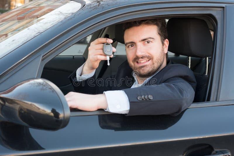 Mens die een autosleutel houden in zijn voertuig gezet stock afbeeldingen