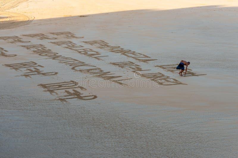 Mens die een bericht in het zand schrijven royalty-vrije stock fotografie