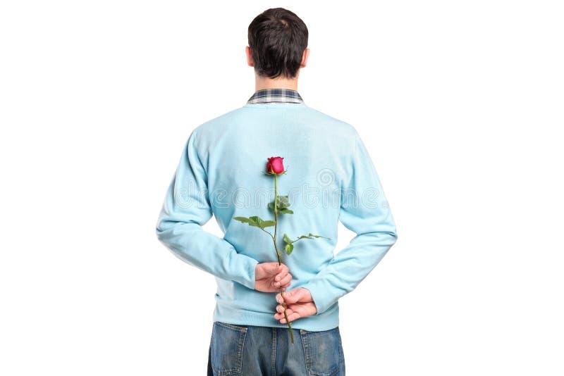 Mens die een bloem achter zijn rug verbergt stock fotografie