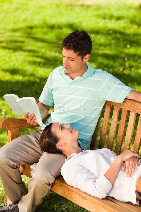 Mens die een boek met zijn meisje leest stock afbeelding