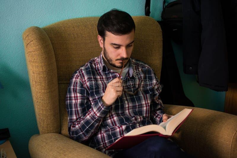 Mens die een boek op bank in zijn huis lezen royalty-vrije stock fotografie