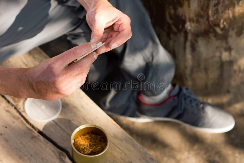 Mens die een cannabisverbinding rollen stock afbeeldingen