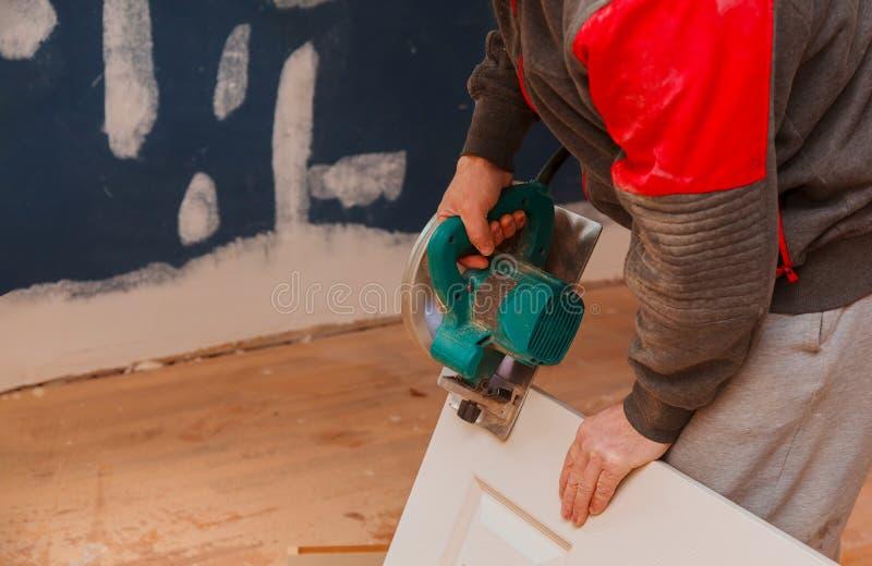mens die een cirkelzaag voor scherpe houten deurbouw en huisvernieuwing gebruiken, reparatiehulpmiddel royalty-vrije stock fotografie