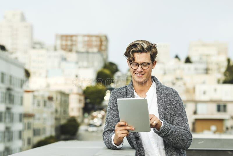 Mens die een digitale tablet gebruiken bij een dak in San Francisco stock fotografie