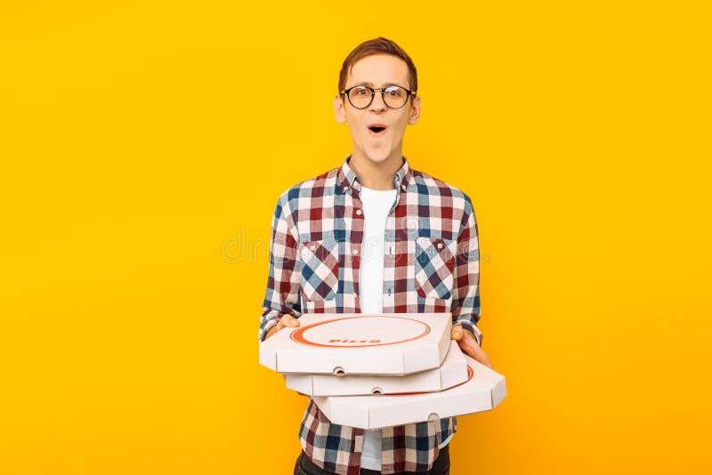 Mens die een doos van pizza op een gele achtergrond houden royalty-vrije stock fotografie