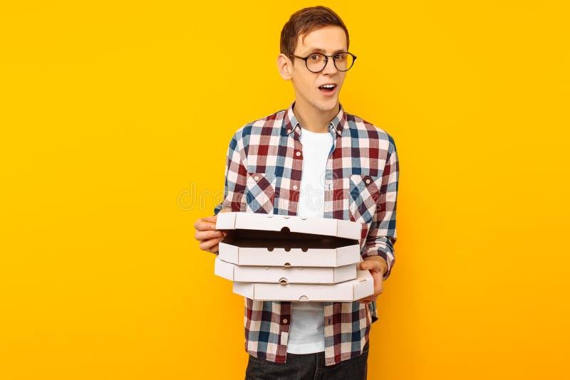 Mens die een doos van pizza op een gele achtergrond houden royalty-vrije stock foto's