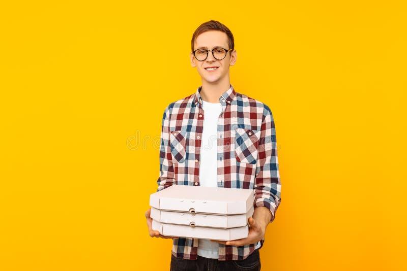 Mens die een doos van pizza op een gele achtergrond houden stock fotografie