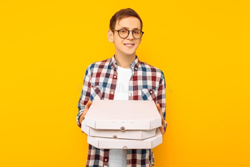 Mens die een doos van pizza op een gele achtergrond houden stock afbeelding