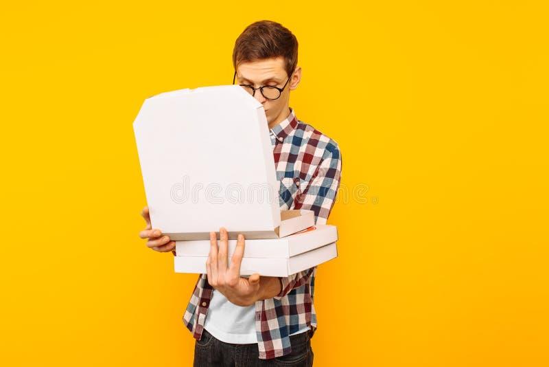 Mens die een doos van pizza op een gele achtergrond houden royalty-vrije stock foto