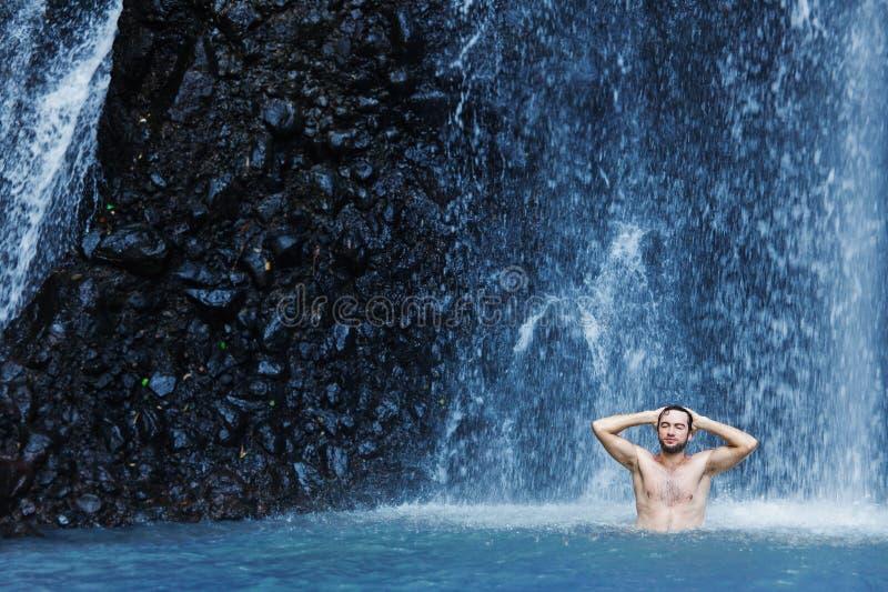 Mens die een douche in waterval hebben stock afbeeldingen