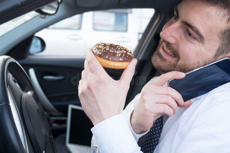 Mens die een doughnut eten en op de telefoon drijfauto spreken stock foto
