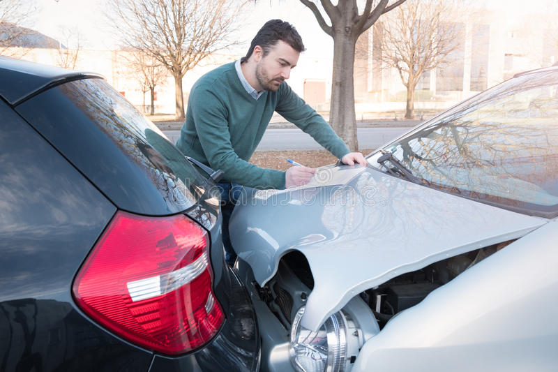 Mens die een eis van de autoverzekering schrijven royalty-vrije stock afbeelding