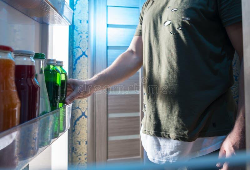 Mens die een fles van drank van zijn koelkast selecteren stock foto's