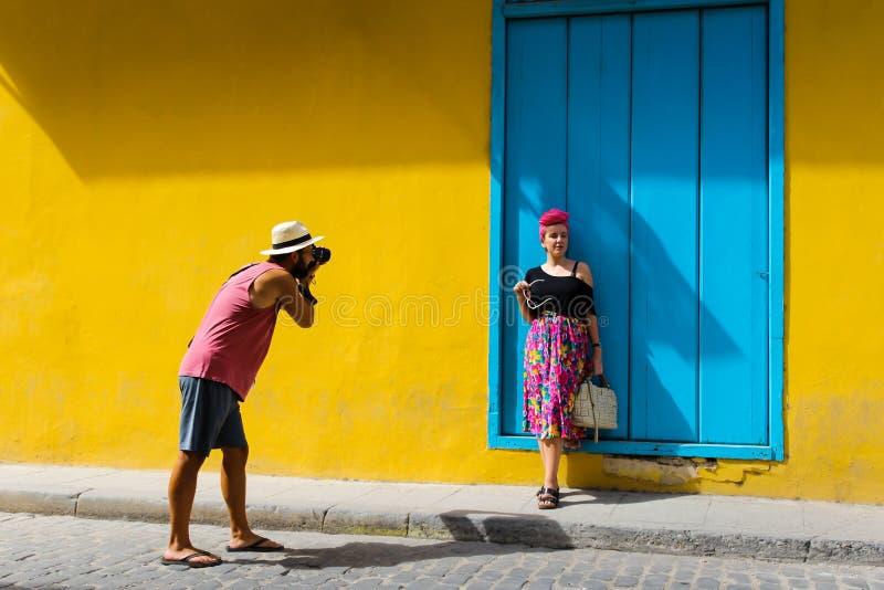 Mens die een foto van een meisje nemen tegen een gele muur royalty-vrije stock foto