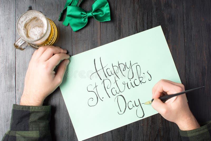 Mens die een Gelukkige St Patrick dagkaart schrijven royalty-vrije stock fotografie